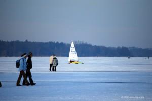 Eissegler und Spaziergänger auf zugefrorenem See