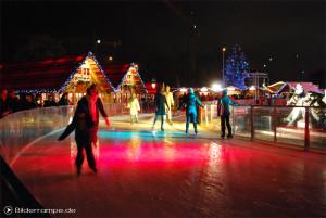 Menschen auf der Eislaufbahn rund um den Neptunbrunnen